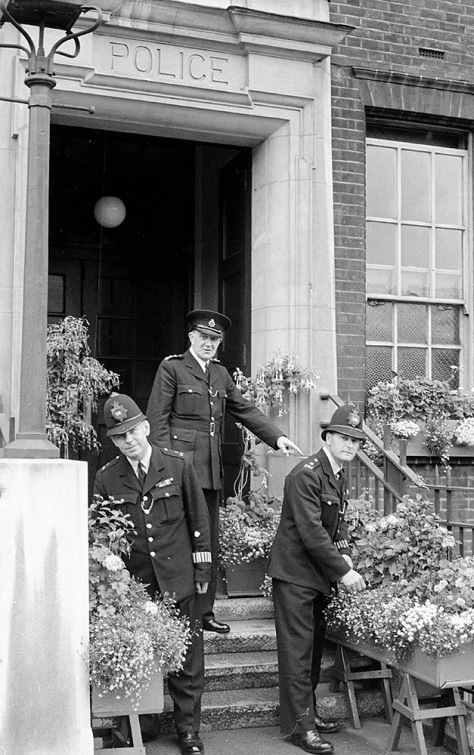 Local police celebrate the local floral competition at their station in Walham Green, an area now absorbed into Fulham Broadway